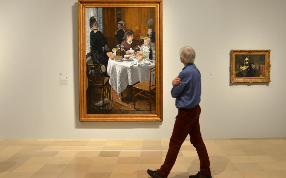 """A visitor looks at Claude Monet's """"The Luncheon"""" from 1868/69. This painting, along with another with the same name from 1873, are the centerpieces of the the """"Monet and the Birth of Impressionism"""" exhibit at the Städel in Frankfurt, Germany."""