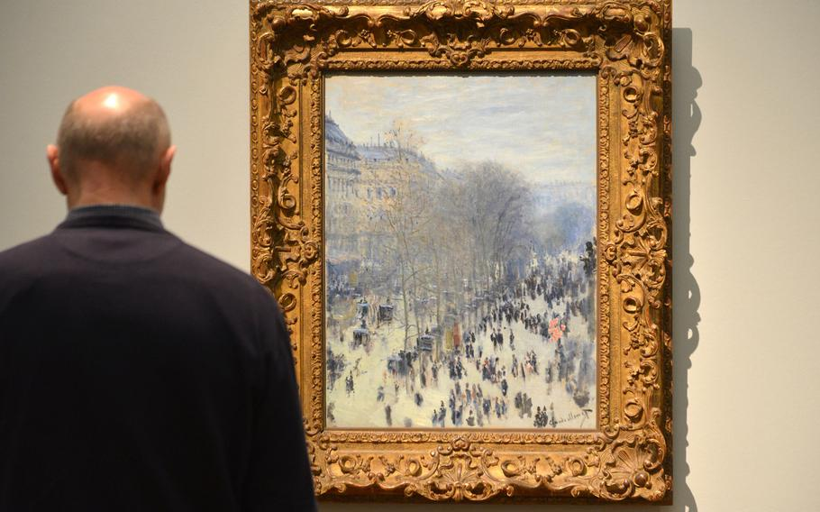 """A visitor to the """"Monet and the Birth of Impressionism"""" exhibit at the Städel in Frankfurt, Germany, takes a look at Claude Monet's """"Boulevard des Capucines"""" from 1873/74. To art critics then and today it is an important piece of art, as for the first time it depicts the impression of a city in motion"""