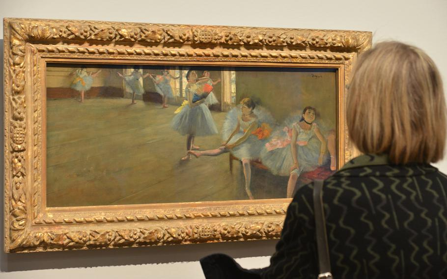 """A visitor to the """"Monet and the Birth of Impressionism"""" exhibit at the Städel in Frankfurt, Germany, gets a closer look at Edgar Degas' """"Dancers in the Classroom"""" from about 1880."""