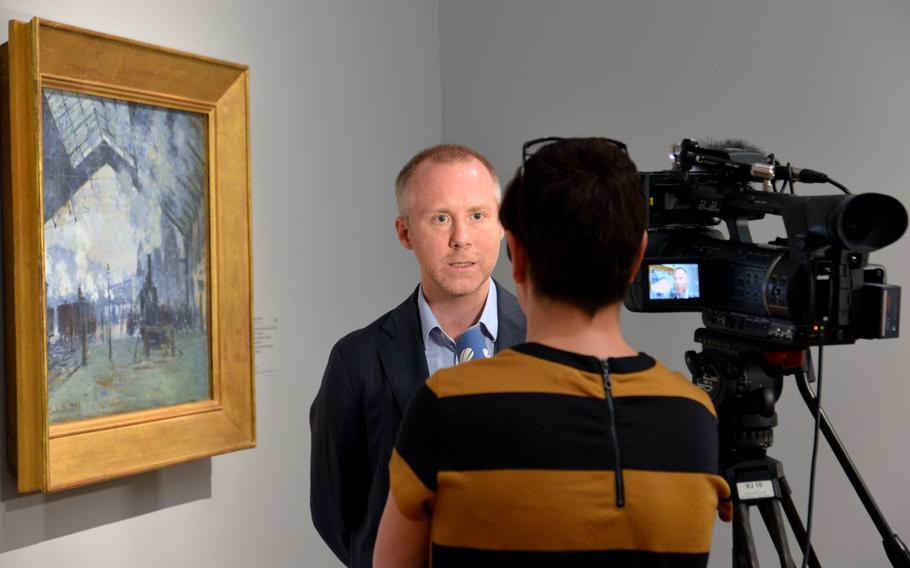 """Felix Kämer, the curator of the """"Monet and the Birth of Impressionism"""" exhibit at the Städel in Frankfurt, Germany, is interviewed standing in front of Claude Monet's """"Saint Lazare Station. Arrival of a Train."""" The exhibit is open until June 21, 2015."""