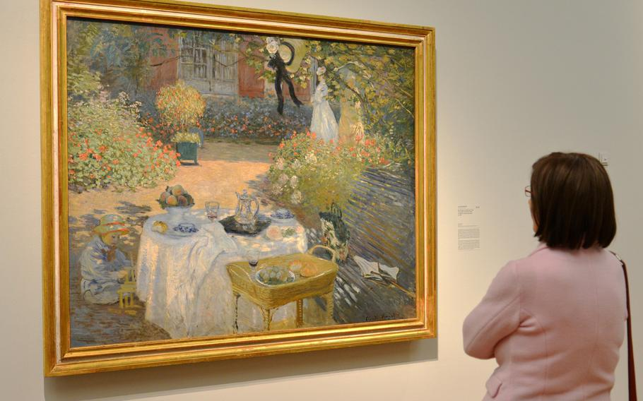 """A visitor looks at Claude Monet's """"The Luncheon"""" from 1873. This painting, along with another with the same name from 1868/69, are the centerpieces of the the """"Monet and the Birth of Impressionism"""" exhibit at the Städel in Frankfurt, Germany."""