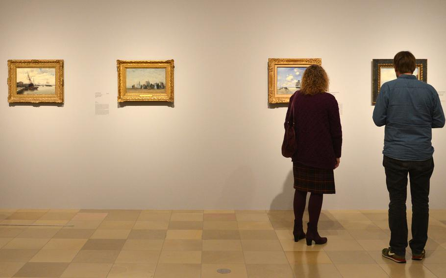 """Visitors to the """"Monet and the Birth of Impressionism"""" exhibit at the Städel in Frankfurt, Germany, examine the artworks on display. The exhibit runs until June 21, 2015."""