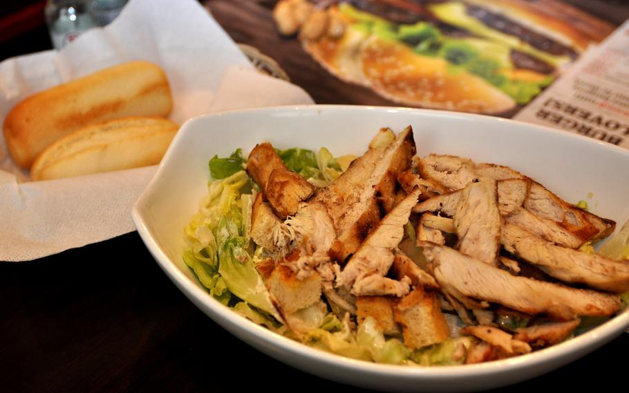 The chicken Caesar salad at Roadhouse Grill is loaded with chicken. A pair of rolls comes along as a side.