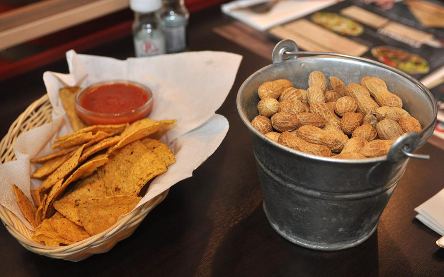 Diners at Roadhouse Grill get a tray of chips and salsa and a small bucket full of peanuts to crack open while they wait for their food to be served.