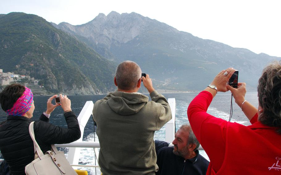 Passengers on a boat tour along the shore of Mount Athos snap photos of one of the 20 monasteries on the peninsula. Boats carrying women must stay about a third of a mile from shore.