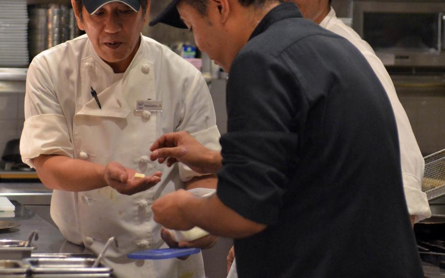 Kitchen staffers go about their business at Roy's Hawaii in Okinawa. All except the kitchen staff are dressed immaculately in white tops, black trousers and ties, and the tables are adorned with white tablecloths, blue napkins and gleaming silverware and crystal.