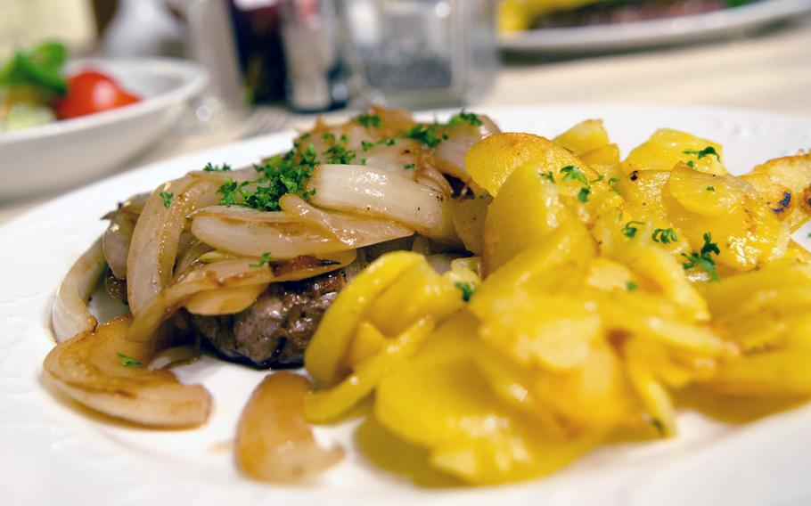 A steak with onions and roasted potatoes at Gastaette Drehpendel, a cozy restaurant in the sleepy Wiesbaden suburb of Bierstadt which offers a range of German and Italian dishes.