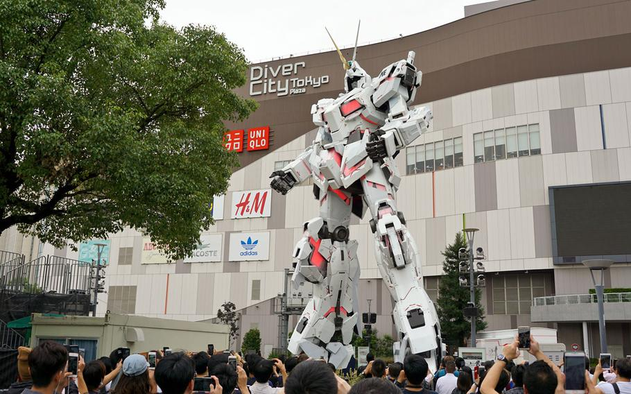 The Unicorn Gundam statue in Odaiba, Tokyo, is pictured halfway through its transformation into battle-ready destroy mode, Thursday, Sept. 28, 2017. The process takes about 10 seconds and occurs several times daily.
