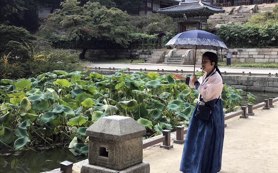 A South Korean guide wearing traditional clothing explains the history of the Buyongji Pond with the Juhamnu Pavilion in the background during a tour of the Secret Garden behind the Changdeokgung Palace in Seoul, South Korea, Sunday, Oct. 8, 2017.