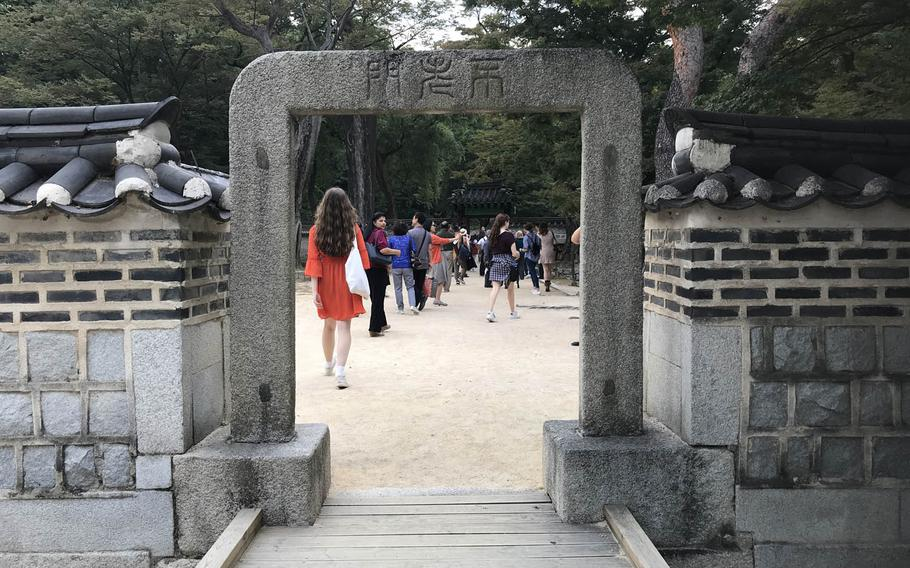 Tourists pass through the Gate of Eternal Youth in the Secret Garden behind the Changdeokgung Palace in Seoul on Sunday, Oct. 8, 2017.