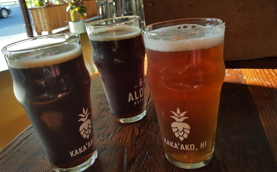 A pair of Portlock Porters stand beside a Manini India Pale Ale at Aloha Beer Company in Honolulu.
