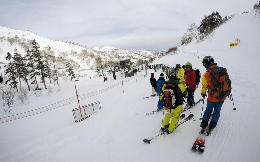 Skiers and snowboarders wait for a lift at Kagura ski resort in Niigata Prefecture, Japan.