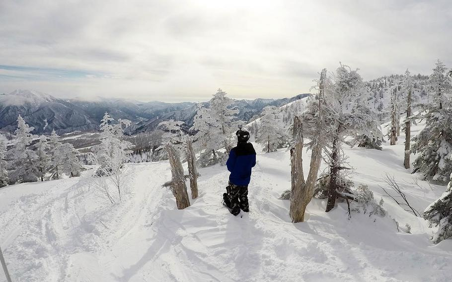 Snowboarder Jerry Sysourath checks out the view from the top of Kagura ski area in Niigata Prefecture, Japan, Friday, Jan. 5, 2018.