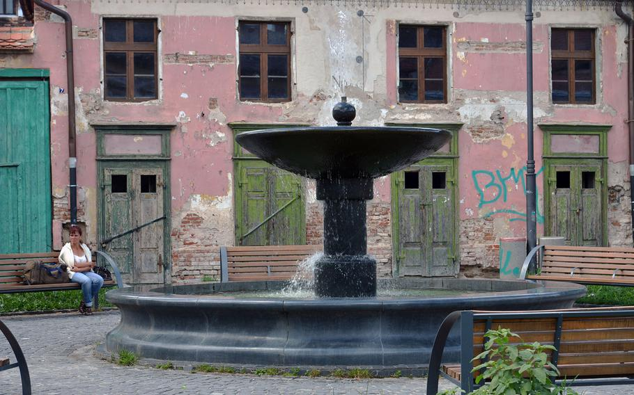 A fountain sprouts water on Piata Coroana in Sibiu's lower town. Although a bit rundown, the flaking pastels of the buildings add to the city's charms.