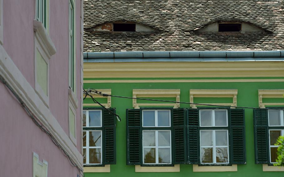 Sibiu, Romania, is a colorful city, with many of its old buildings painted in a variety of colors. The eye-like attic openings sometimes makes it look like the buildings have faces.