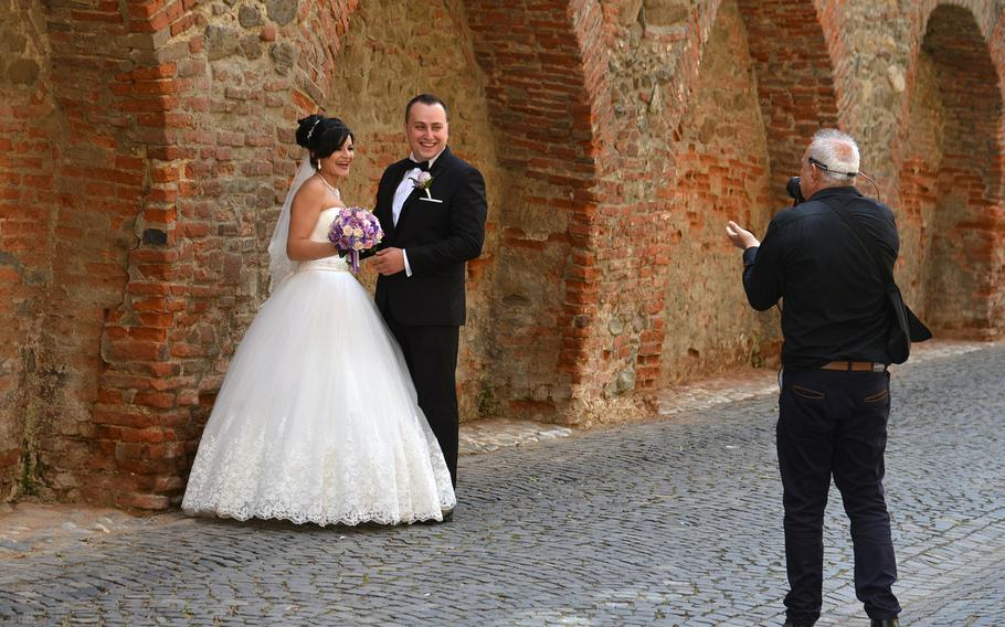 A wedding photographer gives the bride and groom instructions as they pose in front of Sibiu, Romania's old city walls.