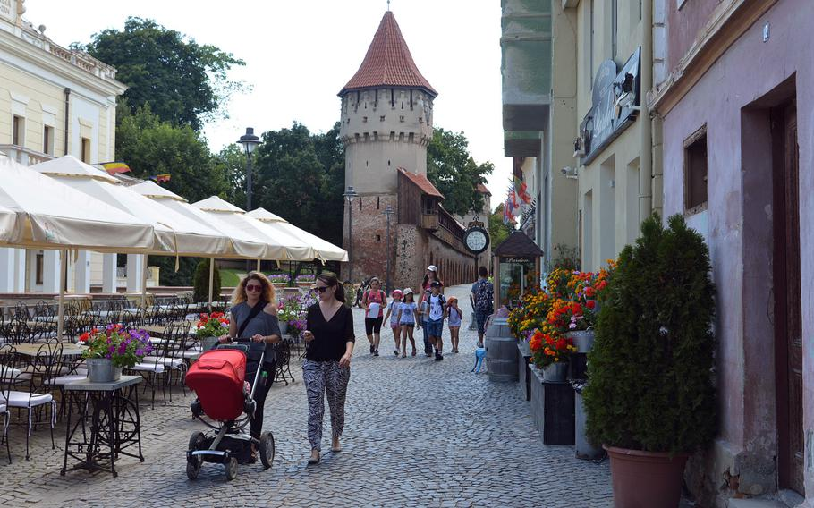 People stroll along the cobblestone lanes of Sibiu, Romania. In the background are the remnants of the city's old city fortifications with the Carpenters' Tower and the Potters' Tower.