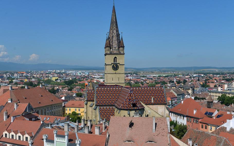 The beautiful tile roof and steeple of Sibiu, Romania's Evangelical l Cathedral as seen from the 13th-century Turnul Sfatului, or Council Tower.