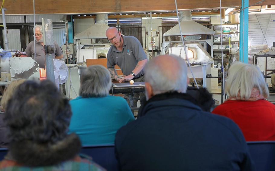 Christopher Stone molds a glass object as he demonstrates to a tour group how to shape glass at Langham Glass in Fakenham, England on Nov. 19, 2019.