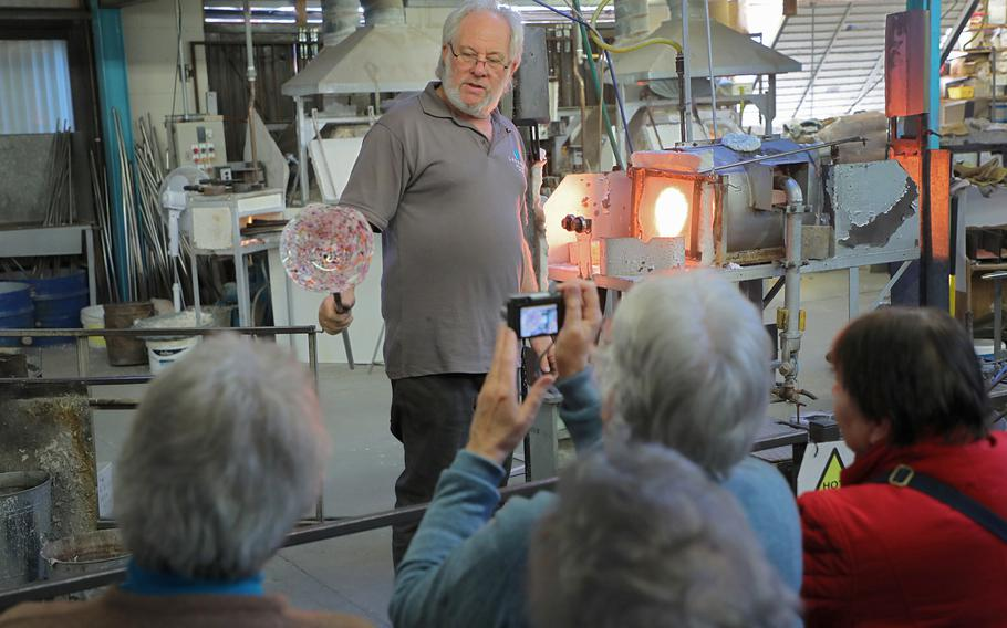 John Wainwright displays a finished glass bowl to a tour group during a demonstration of the art of glass blowing and sculpting at Langham Glass in Fakenham, England on Nov. 19, 2019.