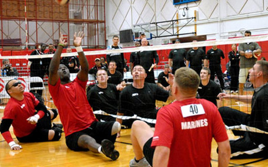 """Gunnery Sgt. Marcus Wilson sets the ball to a teammate during a sitting volleyball game last week at the Warrior Games in Colorado Springs, Colo. He wears a rubber bracelet that says """"courage,"""" and over the last two and half years has become a touchstone for him."""