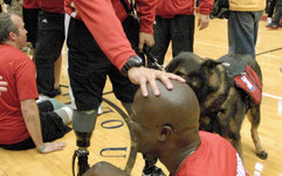 Gunnery Sgt. Marcus Wilson is congratulated by medically retired Gunnery Sgt. Angel Barcenas after winning gold in sitting volleyball at the Warrior Games last week in Colorado Springs, Colo. Barcenas, a double amputee, offered Wilson the encouragement he needed during the early days of his recovery at Walter Reed Medical Center.