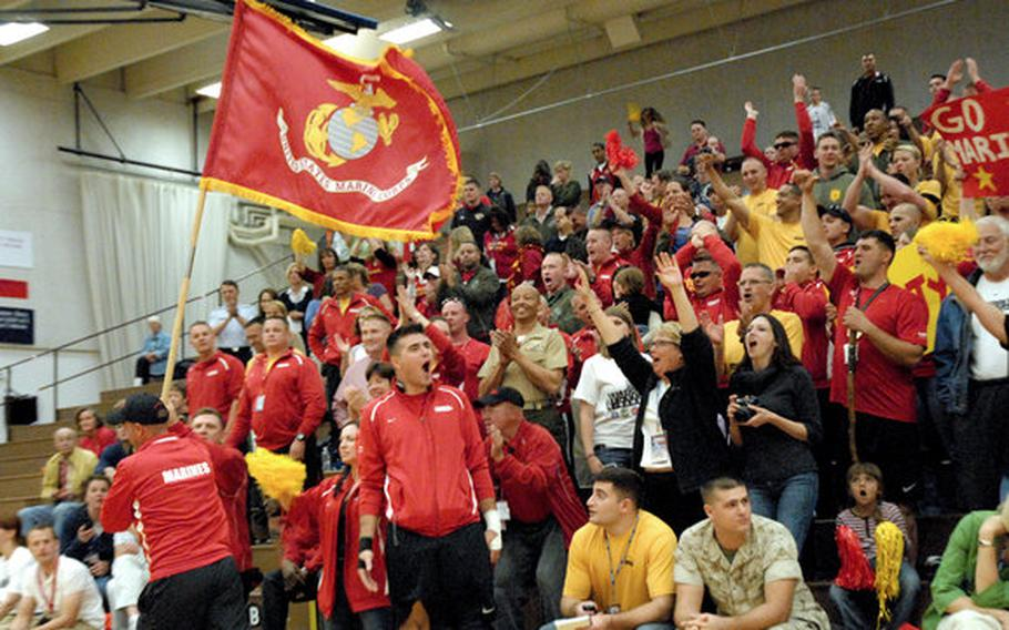To pump up the Marines during the sitting volleyball gold medal game against Army, a Marine runs the service's flag past the crowd last week at the Warrior Games in Colorado Springs, Colo.