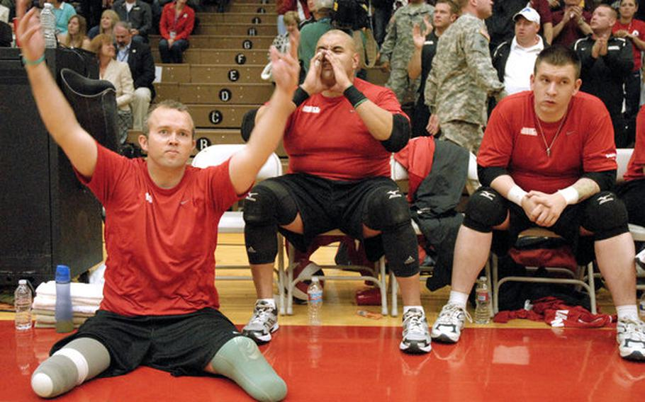 Former Sgt. Bradley Walker, left, a member of the Marine sitting volleyball team, motions to the crowd to get excited as the Marines worked to win gold against Army last week at the Warrior Games in Colorado Springs, Colo. Walker, a combat engineer, was attached to Wilson's unit in Haditha, Iraq, and was hit by an IED two weeks after Wilson was.