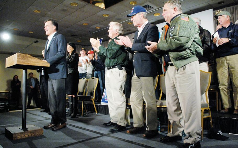 Veterans sharing the stage with Republican presidential hopeful Mitt Romney, left, applaud him as he takes the podium during his campaign appearance on Hilton Head Island, South Carolina, on Friday, January 12, 2012.