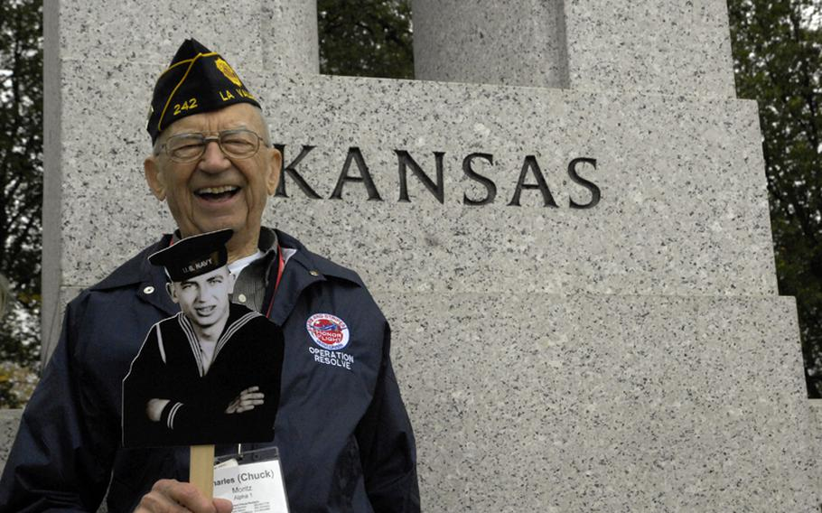 Part of the Stars and Stripes Honor Flight from Wisconsin, veteran Charles Moritz displays an older image of himself by his home state in the World War II Memorial on Nov 3, 2012.