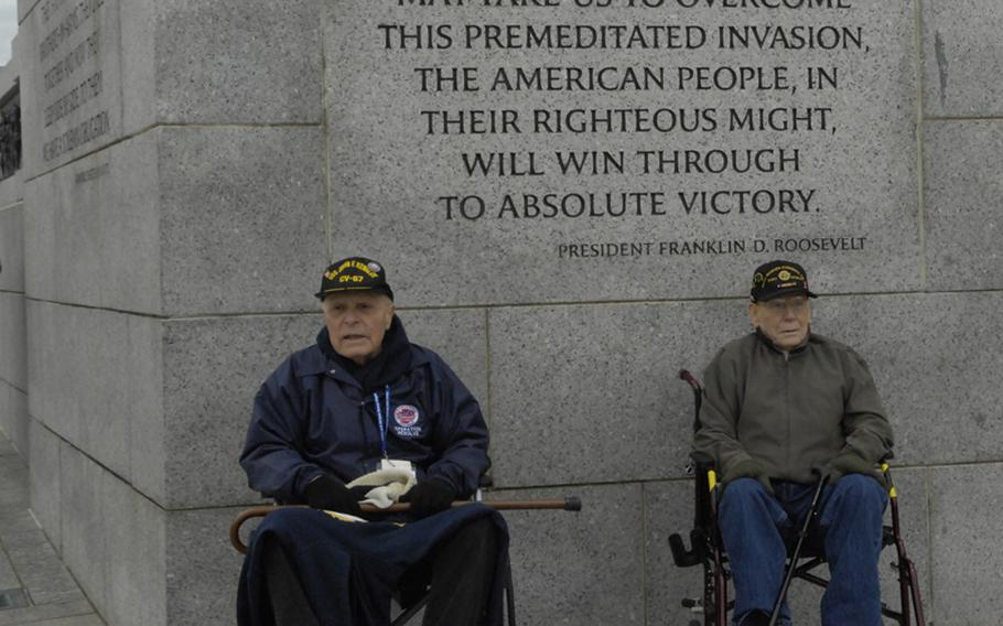 Two veterans take a break from the chilly wind by the Pearl Harbor section of the WWII Memorial.
