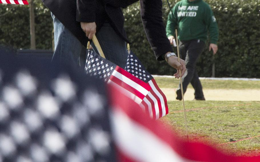 A member of Iraq and Afghanistan Veterans of America (IAVA) plants flags on the National Mall in Washington, D.C., on March. 27, 2014. A total of 1,892 flags were planted, each representing the number of veterans and servicemembers estimated to have committed suicide so far in 2014.