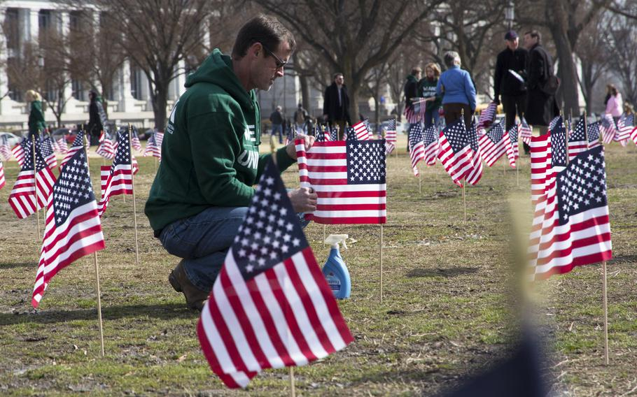 Navy veteran Jeff Hensley, a member of Iraq and Afghanistan Veterans of America (IAVA), unfurls flags on the National Mall in Washington, D.C., on March. 27, 2014. A total of 1,892 flags were planted, each representing the number of veterans and servicemembers estimated to have committed suicide so far in 2014.