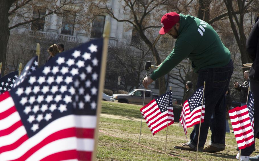 A member of Iraq and Afghanistan Veterans of America (IAVA) helps plant flags on the National Mall in Washington, D.C., on March. 27, 2014. A total of 1,892 flags were planted, each representing the number of veterans and servicemembers estimated to have committed suicide so far in 2014.