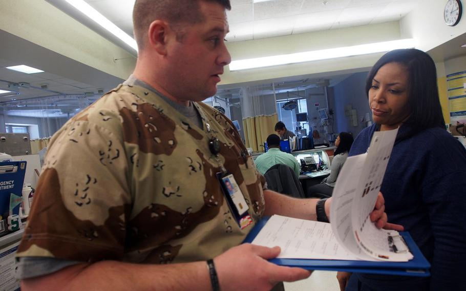 Former Army medic Scott Garbin wears camouflage scrubs on the job, in part to better connect with the fellow veterans he treats at the John Dingell VA Medical Center in Detroit. Garbin is part of a VA program that gives former military health care professionals VA job and helps the department fill a critical shortage.