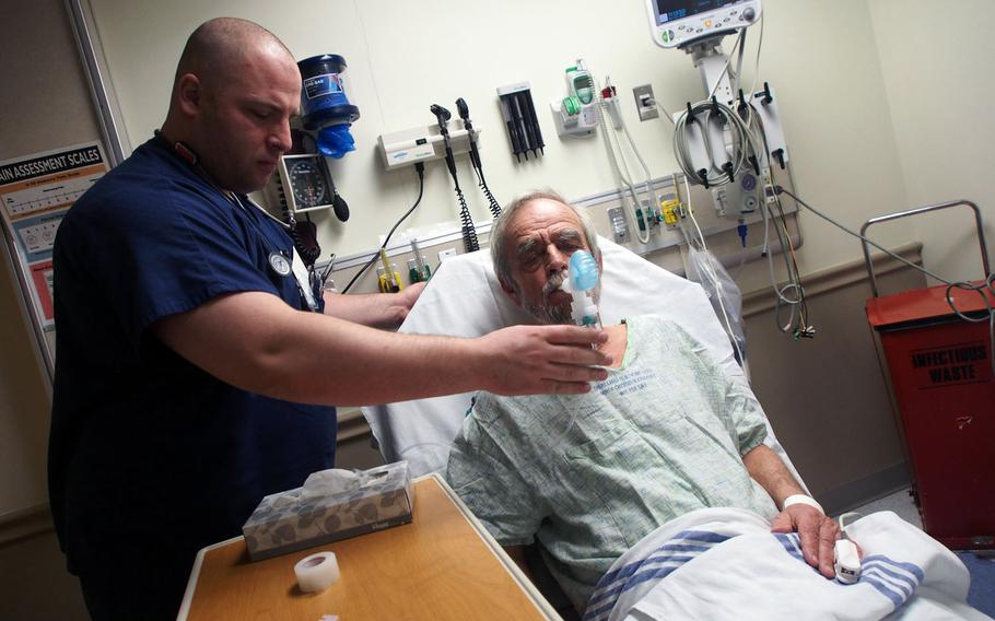 Former Army combat medic Joe Carney attends to a patient at James Lovell Federal Health Care Center in North Chicago, Ill. Like many former medics, Carney struggled to find work after leaving the military, but is now part of a VA program that places such veterans in healthcare jobs.