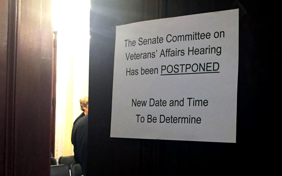 A sign on the hearing room door tells of the postponement of a hearing on May 10, 2017.