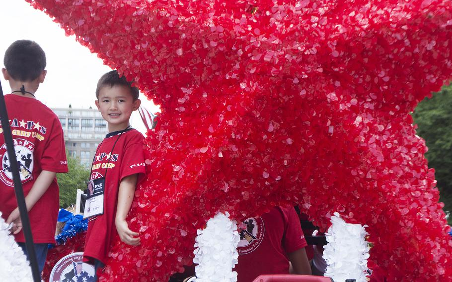 Raiden Prokop, six-years-old, smiles for the camera at the back of the TAPS float before the start of the Memorial Day Parade, Washington, D.C., May 29, 2017. Prokop was there with his older brother Vaughn. Their father, Jason, was a police officer in San Diego in 2011 when - off-duty - he went to aid a driver involved in a collision. Jason, who was in the Army Reserves, was struck by another vehicle and died.