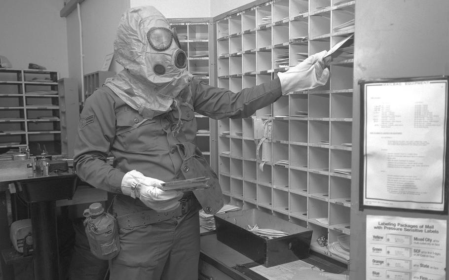 Airman 1st Class Harry Leonard, postal clerk, sorts mail while wearing nuclear-biological-chemical gear during a test to evaluate his unit's ability to perform under fallout conditions in October, 1978.