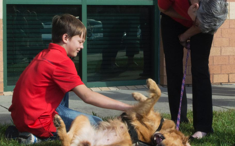 Donovan Nordstrom, 12, plays with Jessi before the start of the Warrior Canine Connection graduation on Oct. 7, 2017.