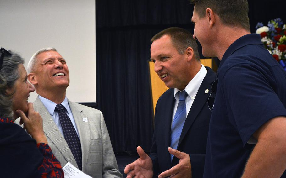 Retired Gen. Jon Paxton Jr. shares a laugh with Rick Yount, executive director of the Warrior Canine Connection, prior to the WCC's graduation ceremony on Oct. 7, 2017.