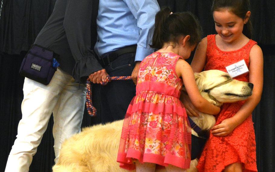 USAF Staff Sgt. Mack Ferrer hugs puppy parent Diane Cadenhead while Ferrer's daughters hug service dog Judy.