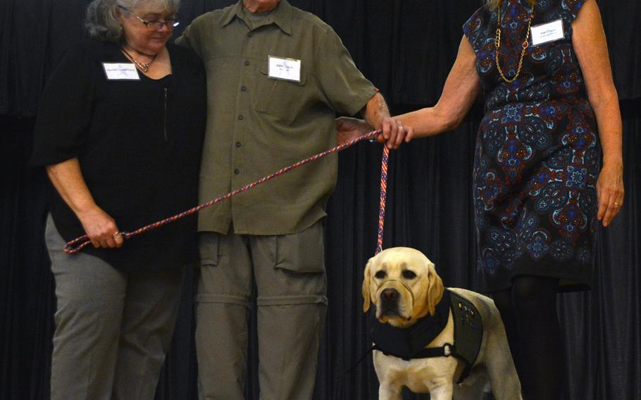 Vietnam veteran John Dixon gets ready to pose for a photo with his support dog Terry. To his right is Pat Dixon and to his left his Maureen Towne, who presented Terry on behalf of his puppy parents Lori and Eric Marshall.