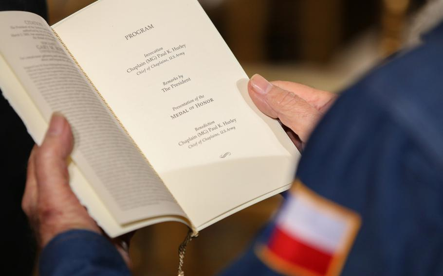 An attendee reads the program for the presentation of retired Army Capt. Gary M. Rose's Medal of Honor at the White House on Oct. 23, 2017.