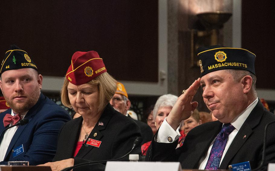 """American Legion Director of Veterans Affairs and Rehabilitation Louis Celli salutes during a hearing on Capitol Hill in Washington, D.C., on Feb. 28, 2018. Next to him is the group's National Commander Denise Rohan, and at left is Matthew Shuman, the group's director for the National Legislative Division. According to Celli, a plan allowing veterans to receive care through the Veterans Choice program only """"upon authorization of the VA secretary, was still included in a spending bill proposal as of Monday, March 19."""
