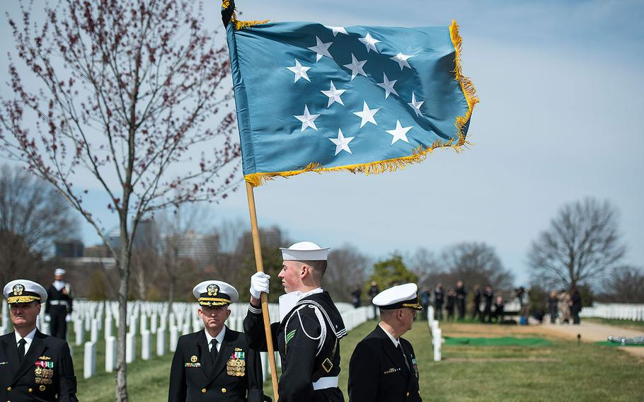 A Personal Color Bearer of The U.S. Navy Ceremonial Guard carries the Medal of Honor flag during the full honors funeral of U.S. Navy Capt. Thomas J. Hudner in Section 54 of Arlington National Cemetery in Virginia on April 4, 2018.