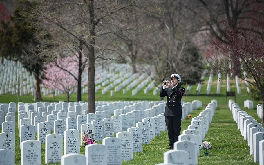 A bugler from The U.S. Navy Band plays Taps during in the full honors funeral of U.S. Navy Capt. Thomas J. Hudner in Section 54 of Arlington National Cemetery, Virginia on Apr. 4, 2018.