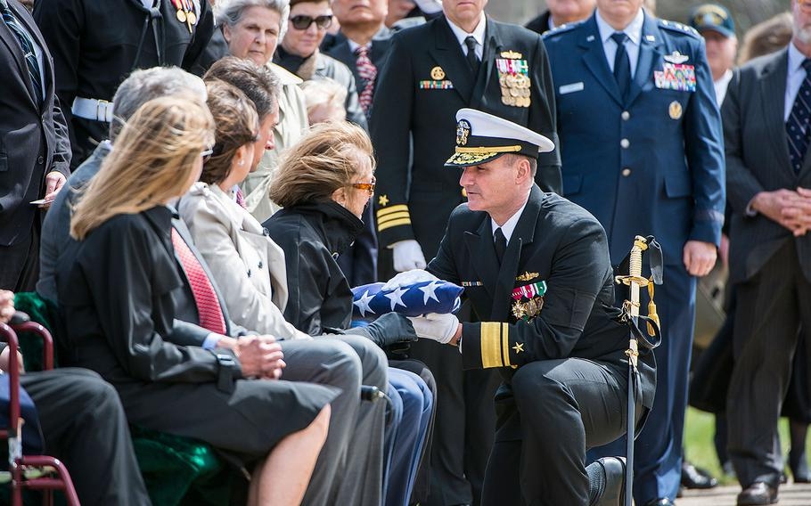 U.S. Navy Rear Adm. William J. Galinis presents the American flag to Georgea Hudner during the full honors funeral of her husband, U.S. Navy Capt. Thomas J. Hudner at Arlington National Cemetery on Wednesday, April 4, 2018.