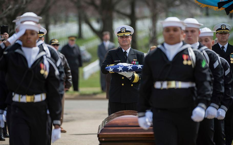 Rear Adm. William J. Galinis prepares to present the national ensign to the family of Capt. Thomas J. Hudner Jr. at Arlington National Cemetery on Wednesday, April 4, 2018.