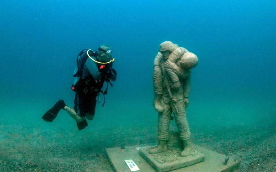 A diver next to the Circle of Heroes Veterans Memorial in the Gulf of Mexico.